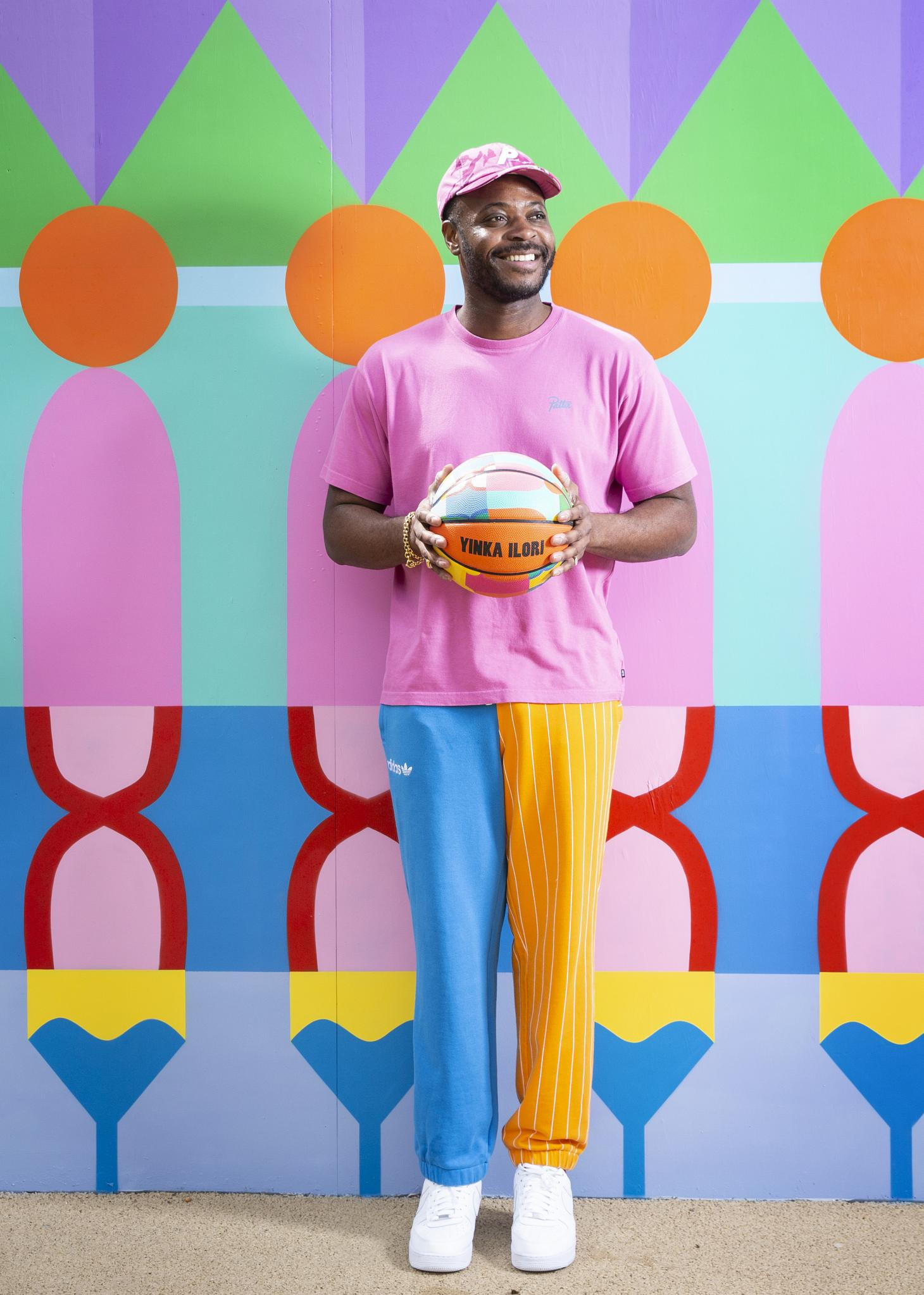 Yinka Ilori holding a colourful basketball at the basketball court he designed for London's Canary Wharf Estate, May 2021