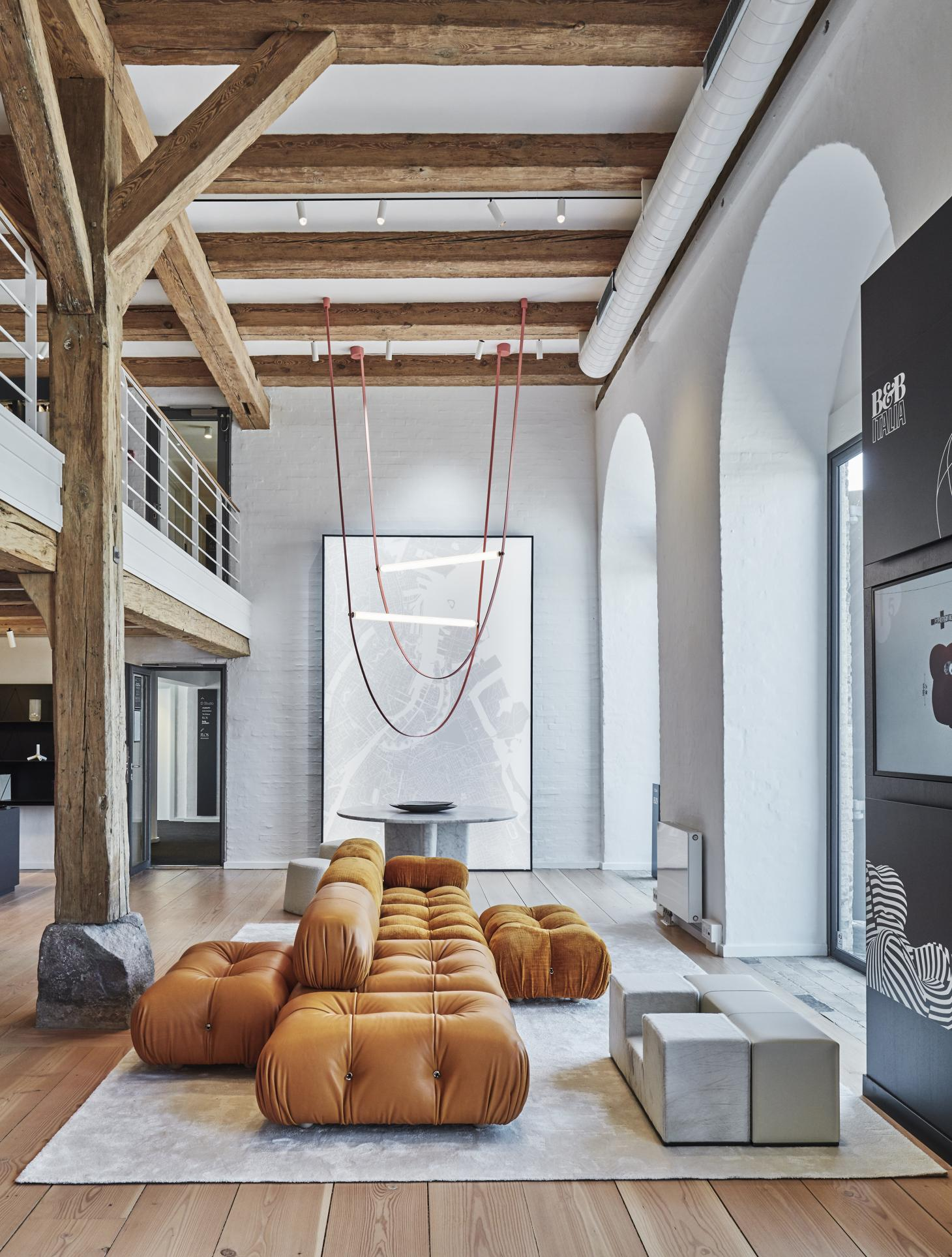 The showroom's ground floor with the Camaleonda modular sofa by Mario Bellini in caramel coloured leather and fabric