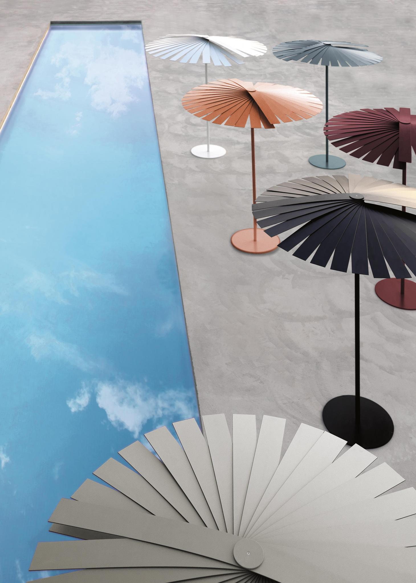 A series of colourful fan shaped parasols by Kettal, near a pool reflecting the sky