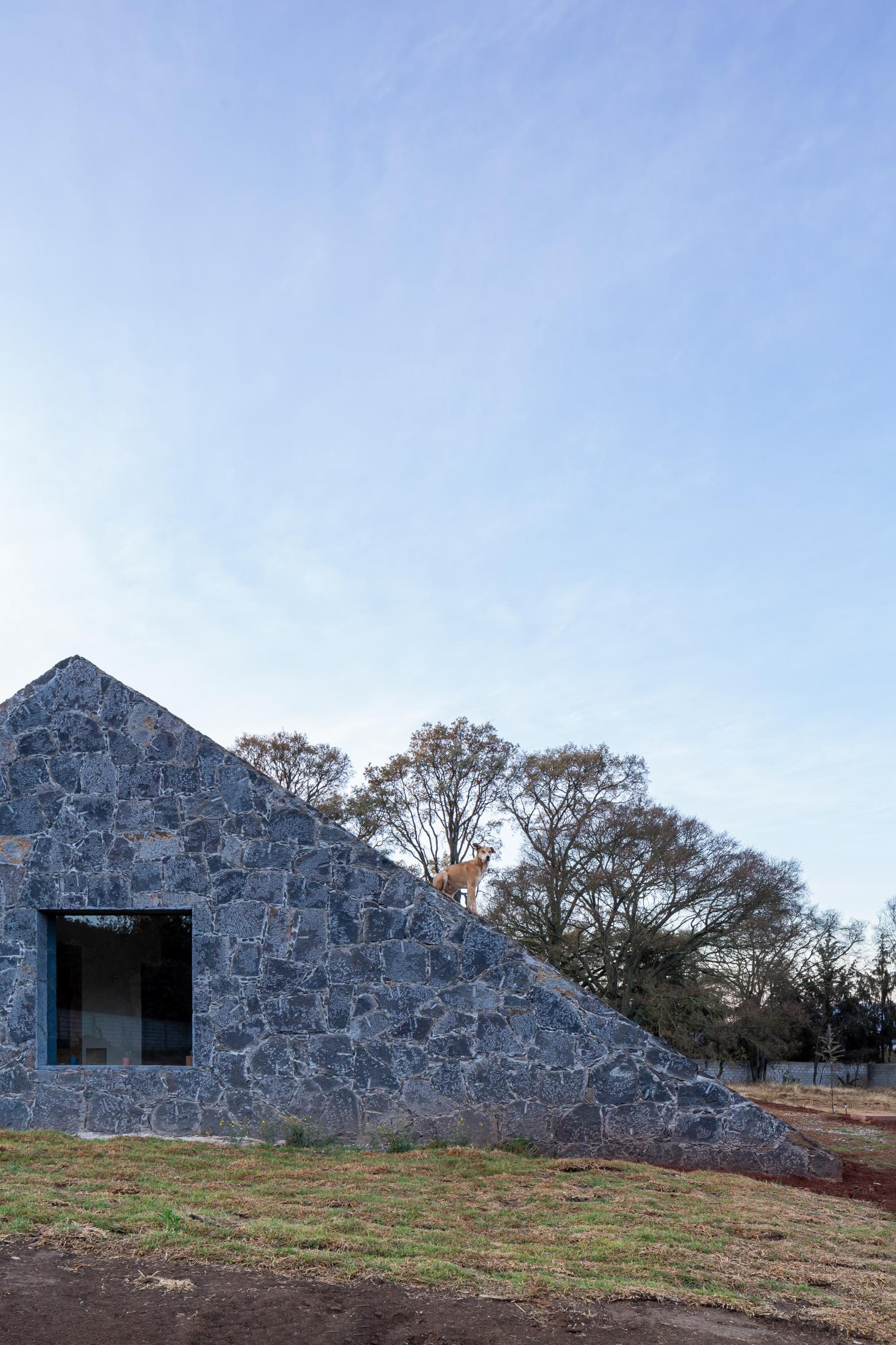 low Mexican house profile with stone wall and pitched roof