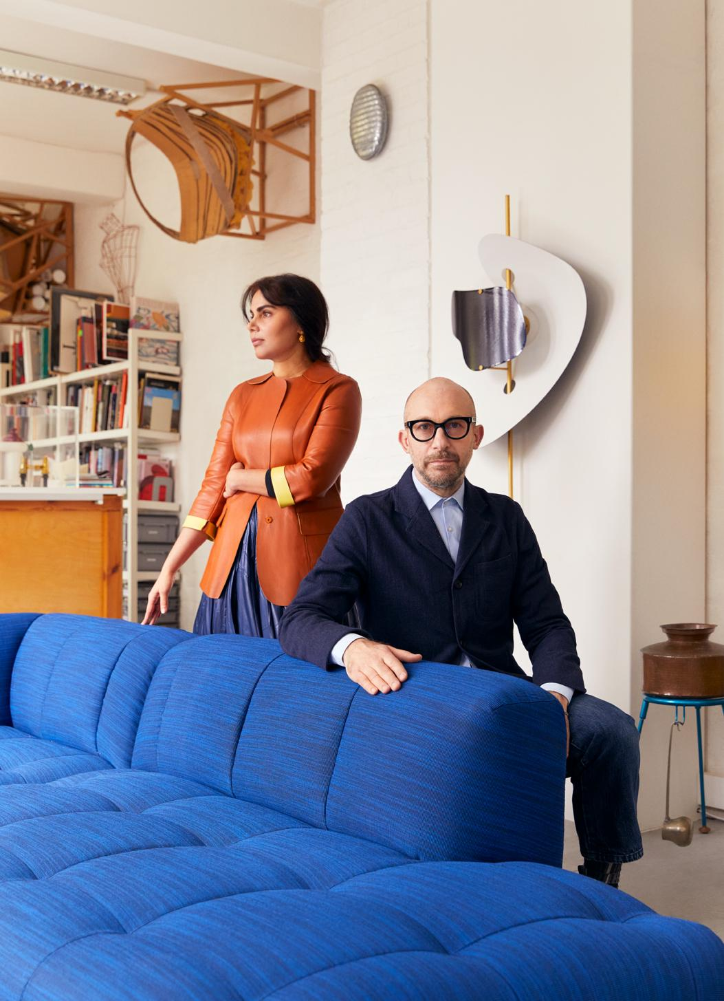Designers Nipa Doshi and Jonathan Levien posing in their London Studio, next to a bright blue version of their Quilton Sofa for Hay