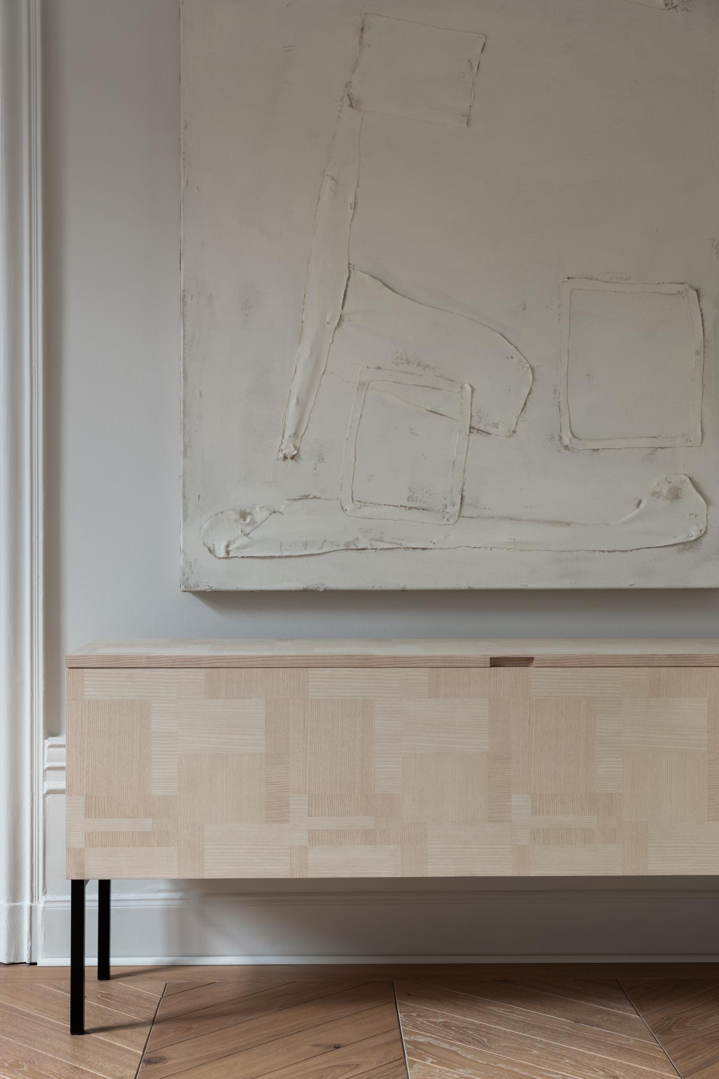 A bench featuring abstract checkered inlaid motif in ash wood, shown under a white painting