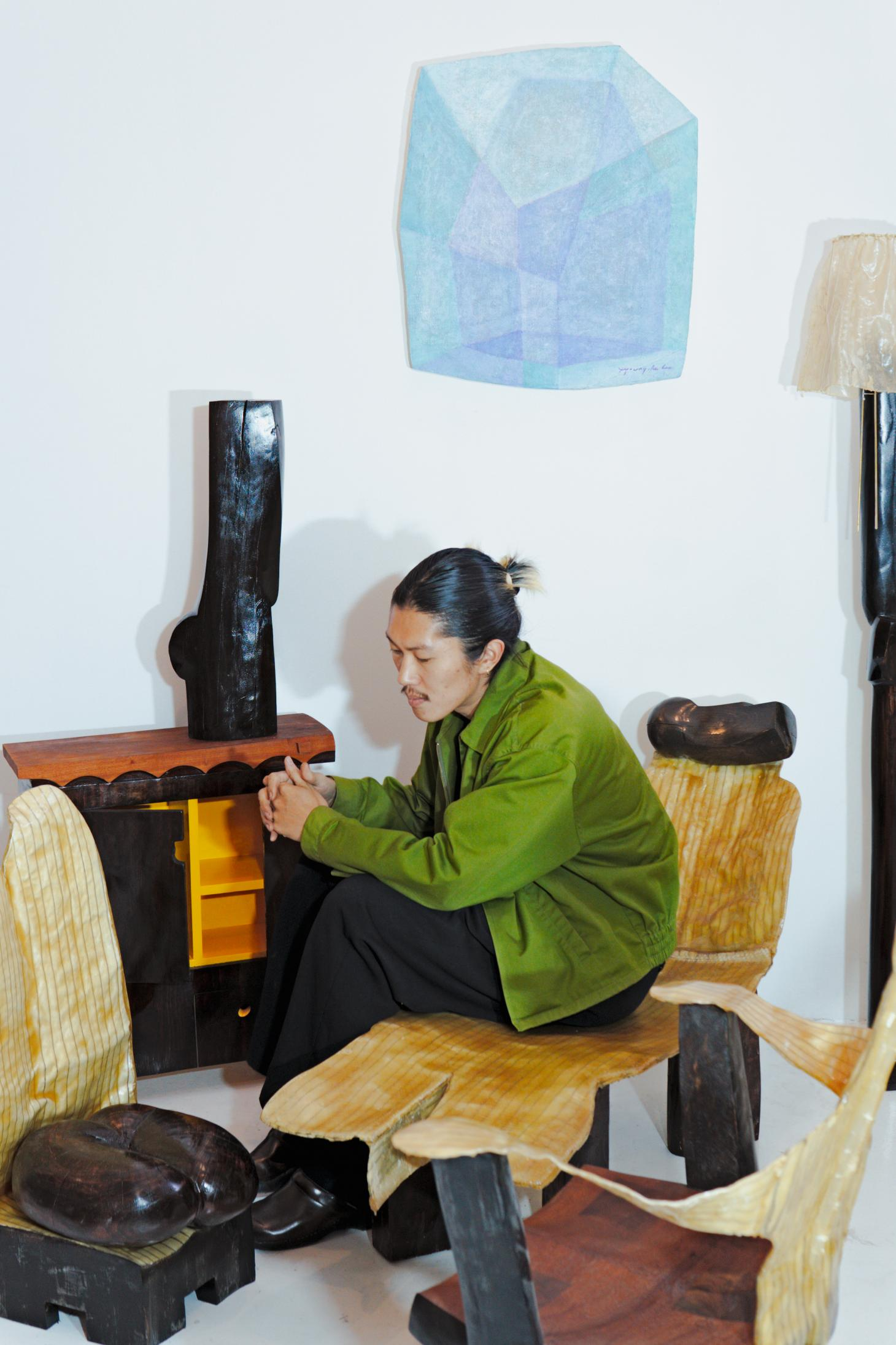 Designer Minjae Kim in his studio surrounded by pieces from the exhibition at Marta Los Angeles including chaise longue, cabinet and wall piece in light blue