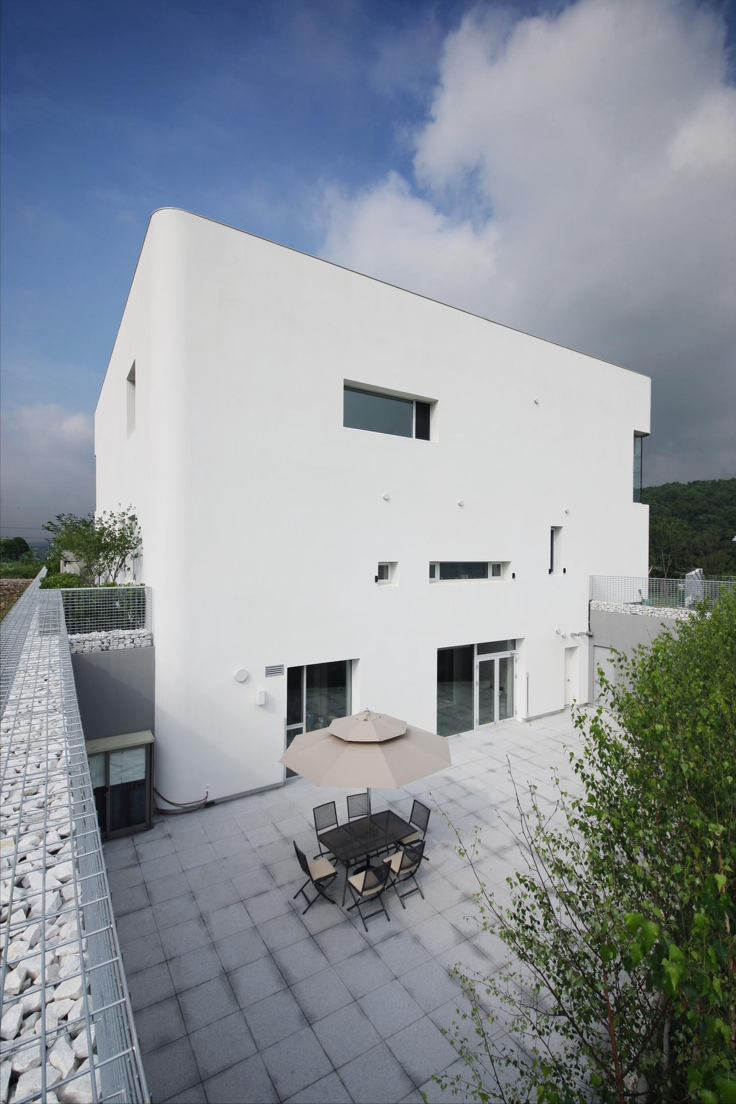 rounded house in South Korea is a white boxy composition with curved corners by architect ChoHelo