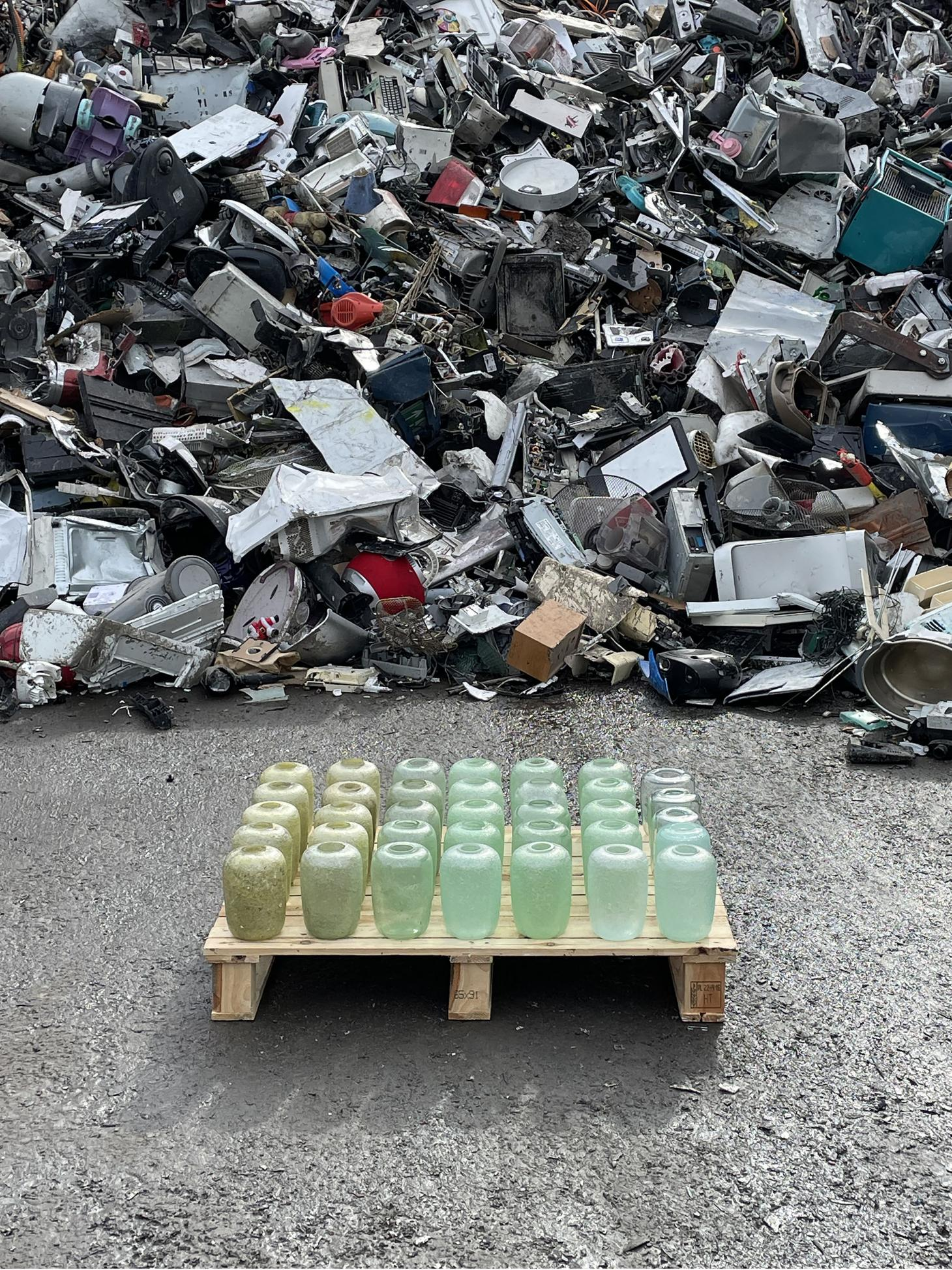 Glass jars in shades of light green with pile of waste in background