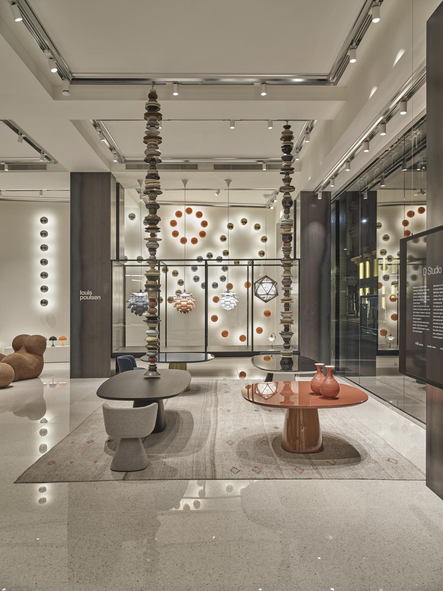 Interiors of D Studio Milano with high ceilings and two dining tables by Monica Armani for B&B in grey and red