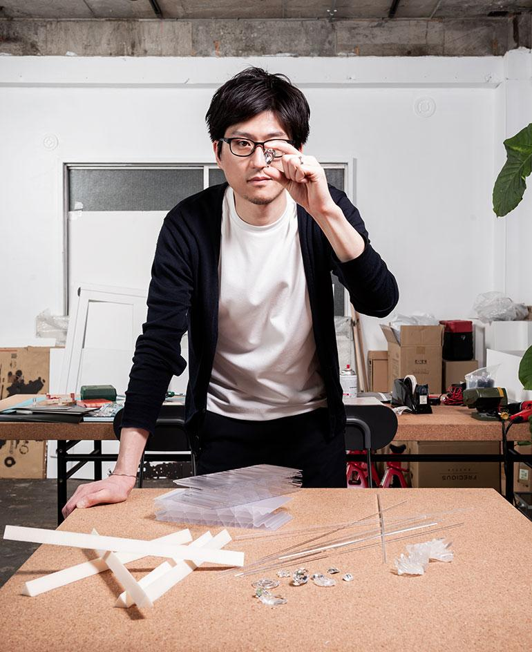 A portrait of designer Satoshi Yoshiizumi, founder of Takt Project, looking through a piece of crystal