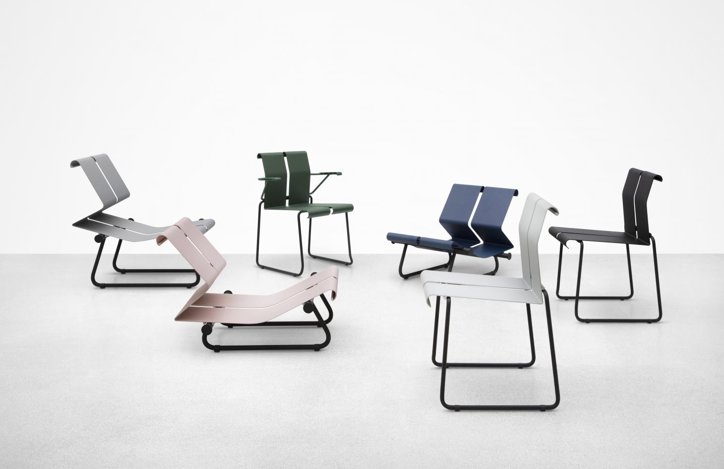A series of chairs whose seat and back are made by a continuous, folded metal sheet, in pink, grey, white, green and blue
