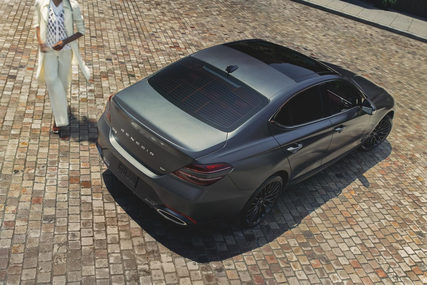 Genesis G70 car, exterior shot in cobbled plaza with woman in white suit beside car