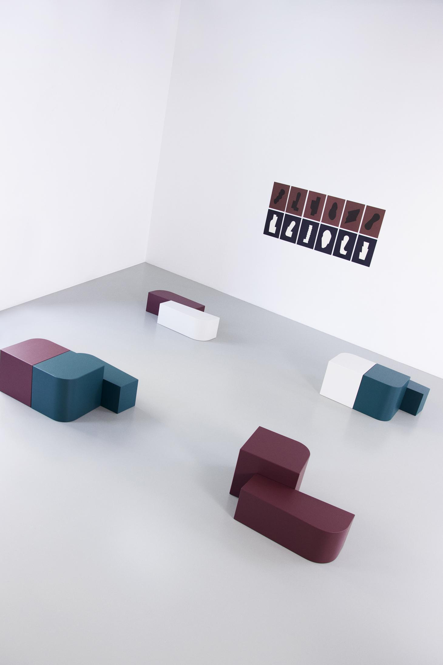 Lacquered side tables in green, burgundy, white with art posters on the wall featuring the same geometric shapes