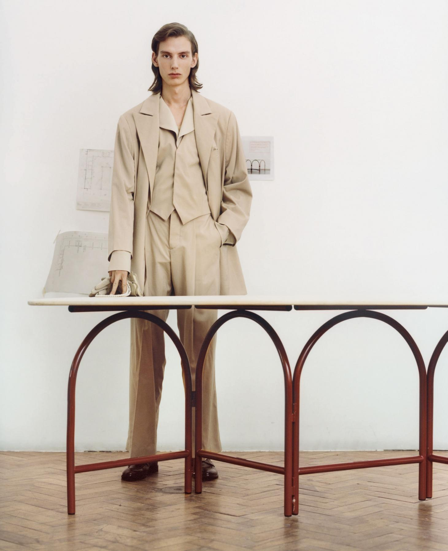 A man stands in beige clothes with his hands across a table
