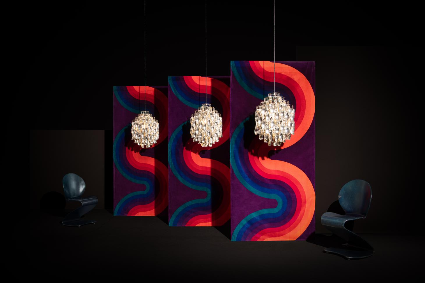 A dark room with a colourful background featuring a sinuous pattern, serving as the backdrop for Verner Panton chandeliers