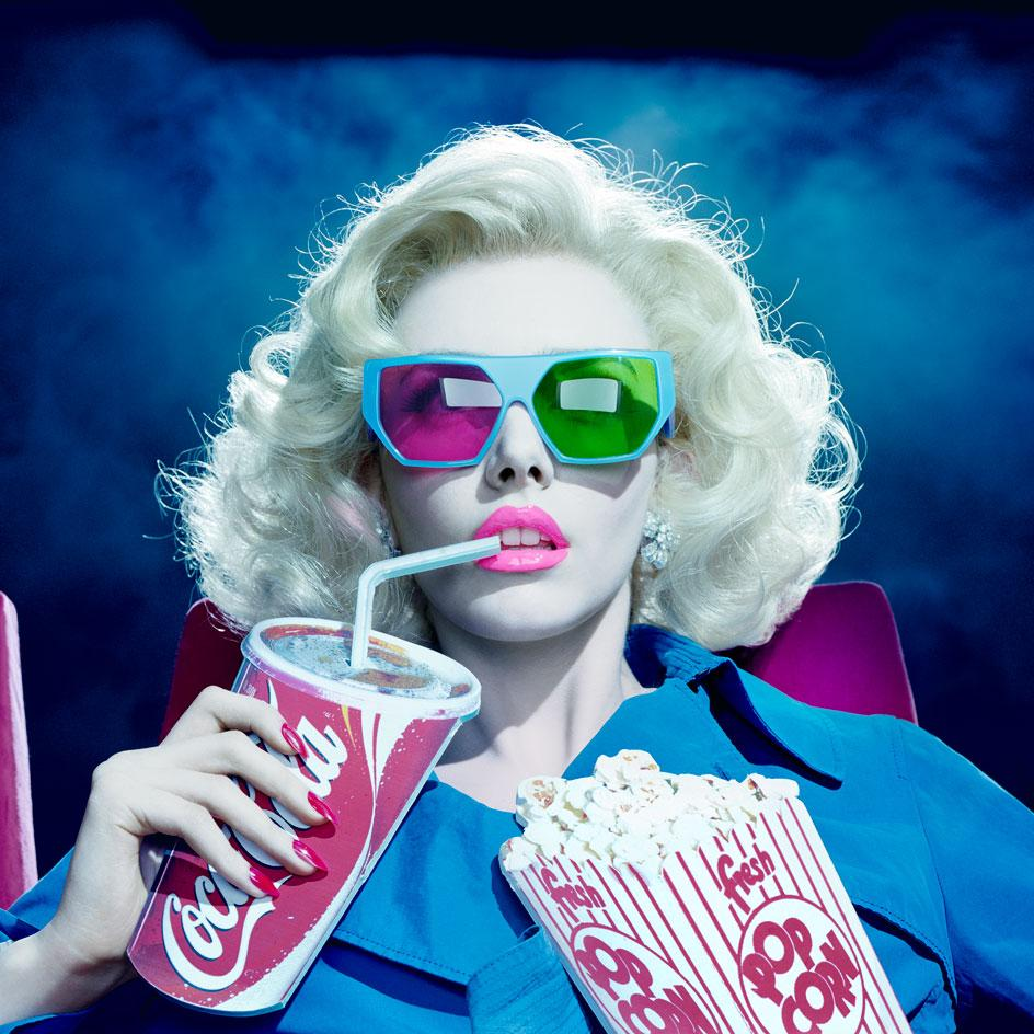 3-D, 2010 by Miles Aldridge which shows a woman wearing 3D glasses and holding a cardboard cut out of popcorn and Coca-Cola