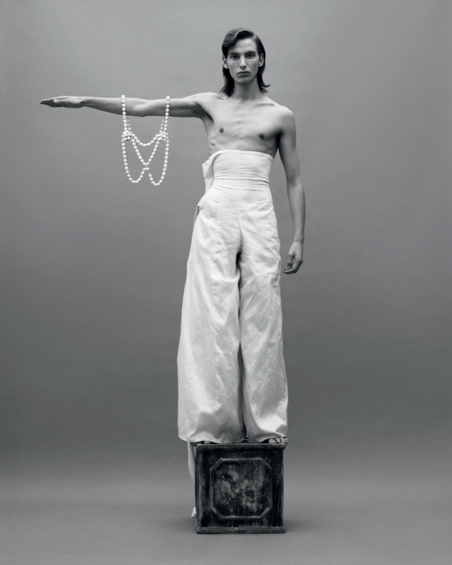 Man stands on a plinth holding a pearl necklace