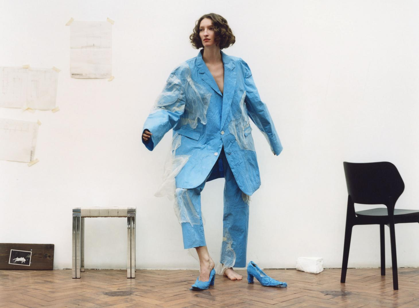 Woman with curly hair stands in a blue plastic suit with blue court heels