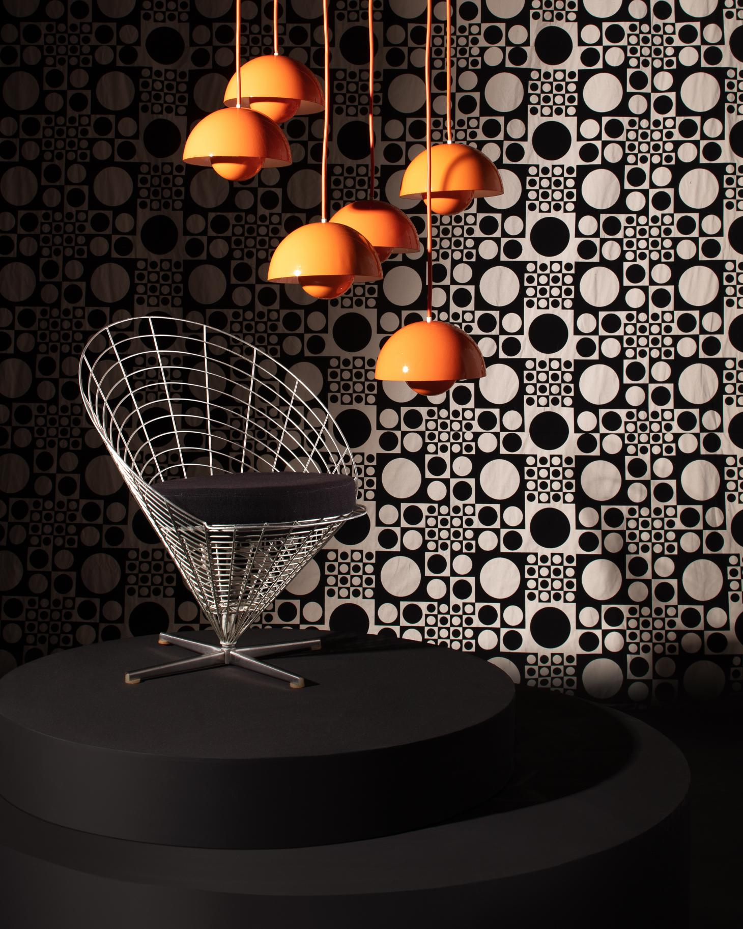 A Wire Cone chair and orange pendant lights by Verner Panton photographed with a black and white optical backdrop