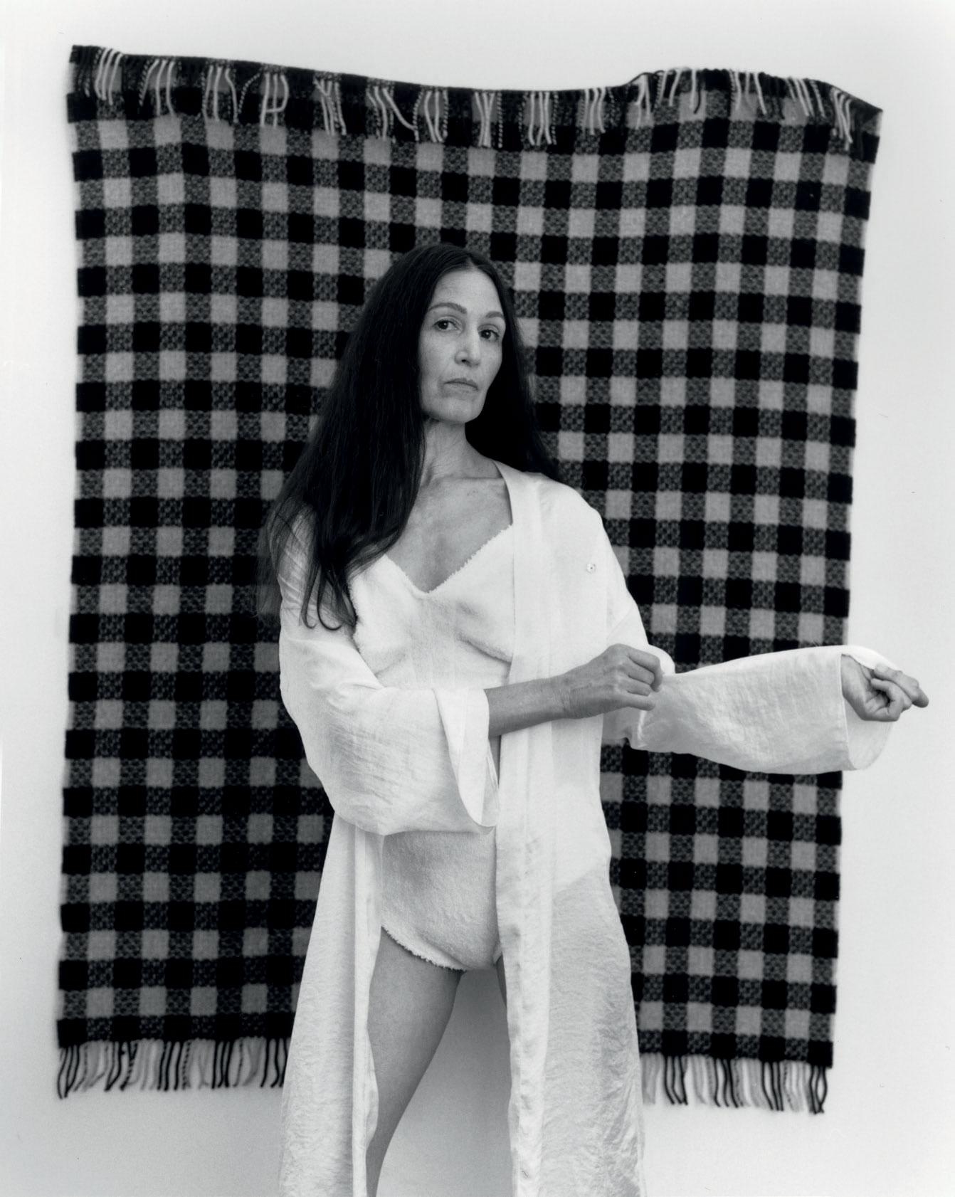 Woman sands in a silk cape against a checkered rug