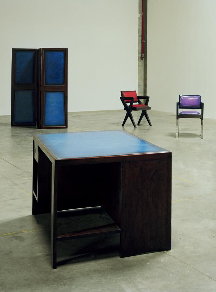 Furniture items in red, purple and blue stand in a concrete room