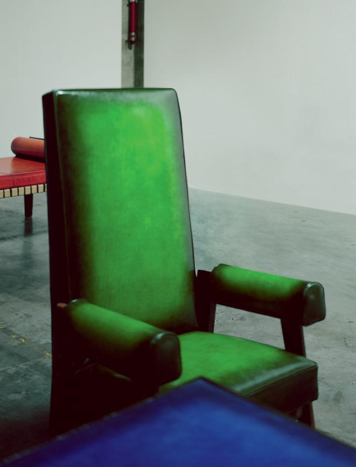 A green armchair is upholstered in Berluti leather