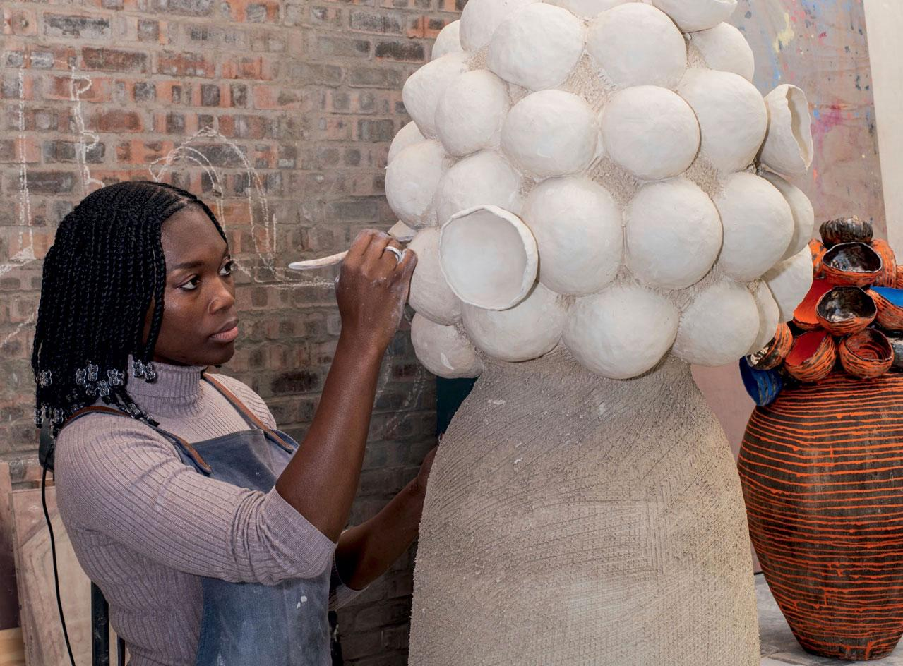 Cape Town-based artist Zizipho Powsa in her studio, working on her Umthwalo series, inspired by the way local women carry heavy loads on their heads. In the background is a finished work titled Umthwalo 4