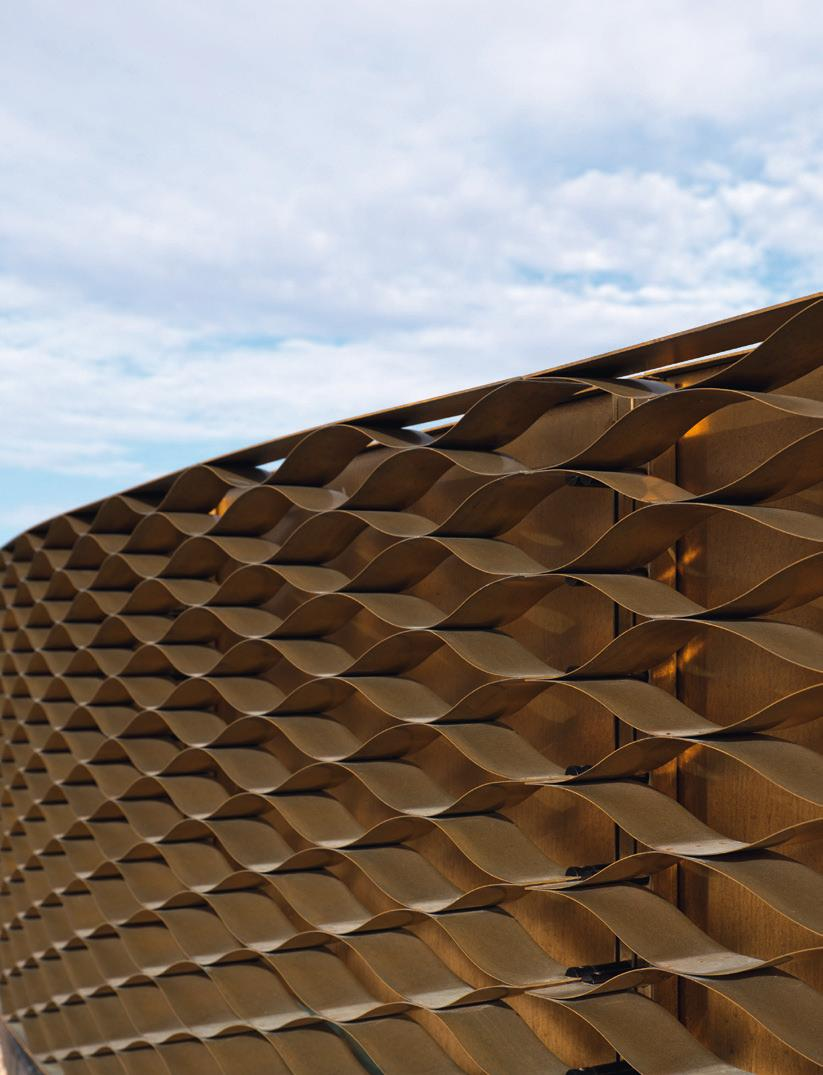 A honeycomb brass veil wraps a building in Switzerland