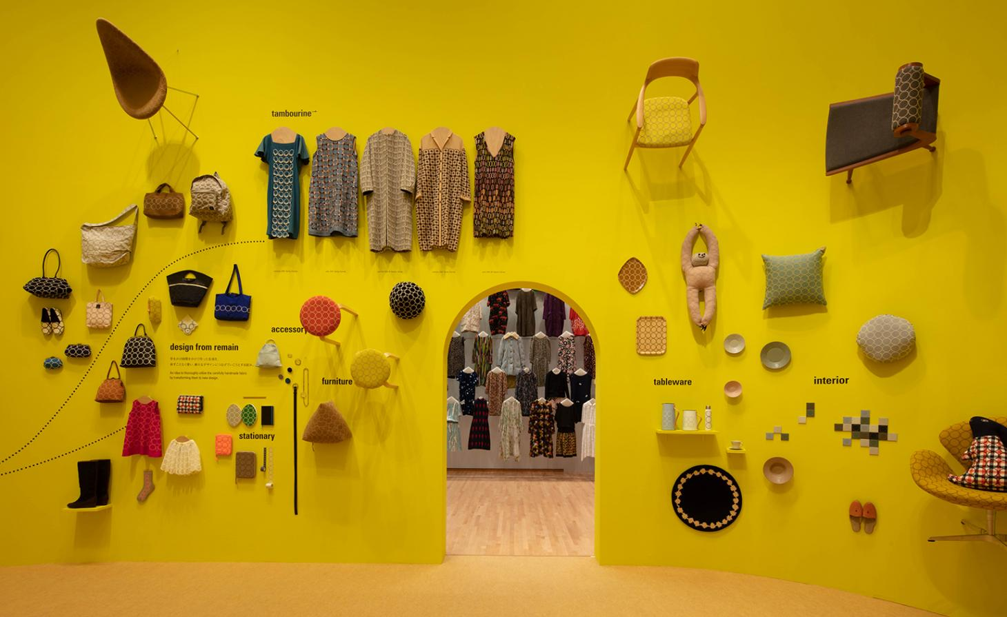 A yellow wall is adorned with clothes and accessories