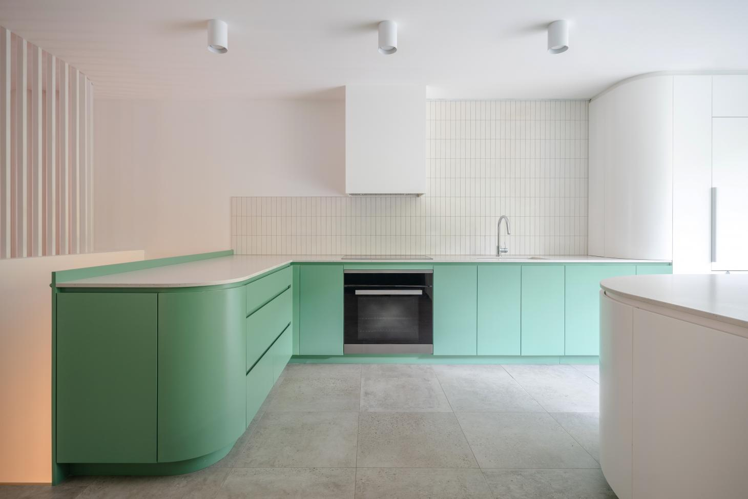 Quesnel Apartment interior with green kitchen by naturehumaine