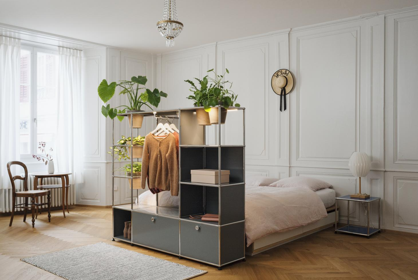 USM Haller bookcase with plant storage in a bedroom with bed and chair and tall ceilings