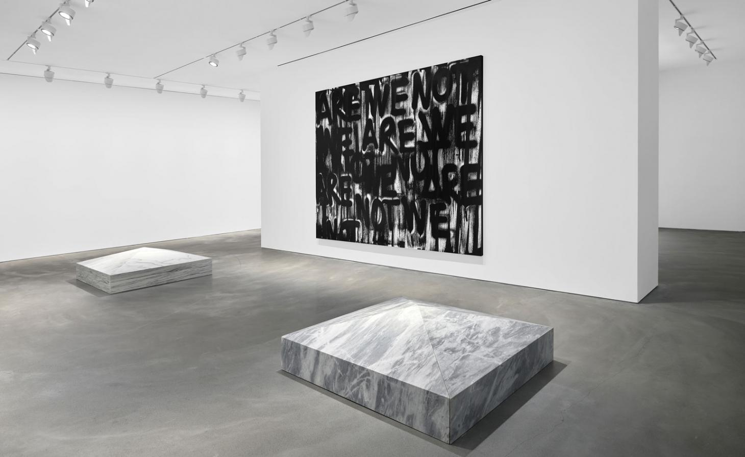 Black and white image of. gallery with marble on the floor and a graffiti image