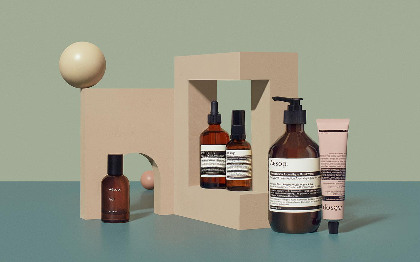 mixture of Aesop products in brown bottles against abstract geometric set of blue and light pink blocks