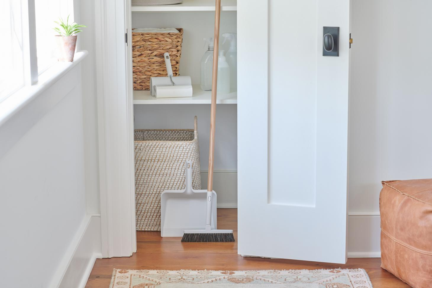 A white wooden closet with a broom and dustpan, lint roller and spray bottles, part of the Muji and Airbnb holiday home essentials kit