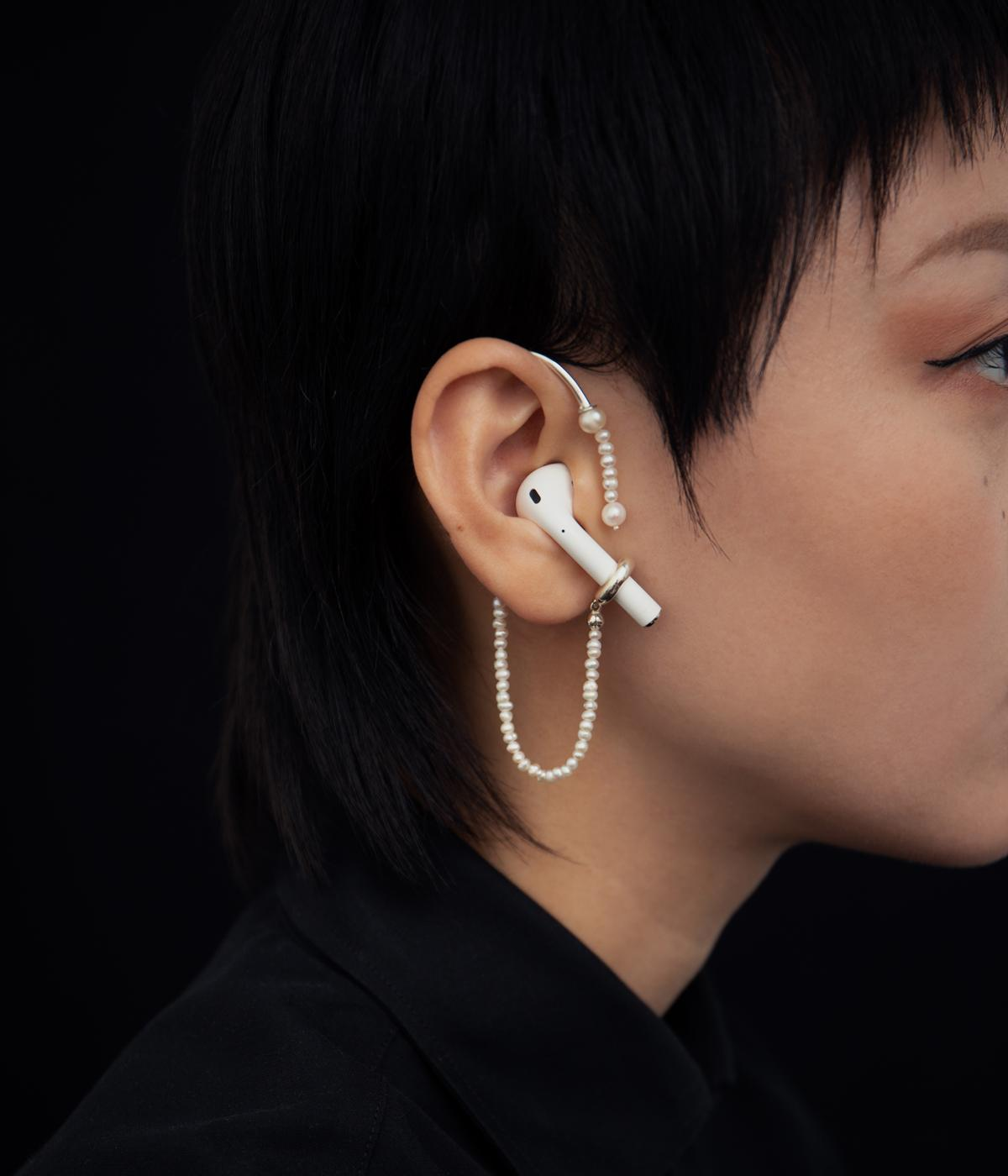 Woman wearing an airpod with pearls dangling round it
