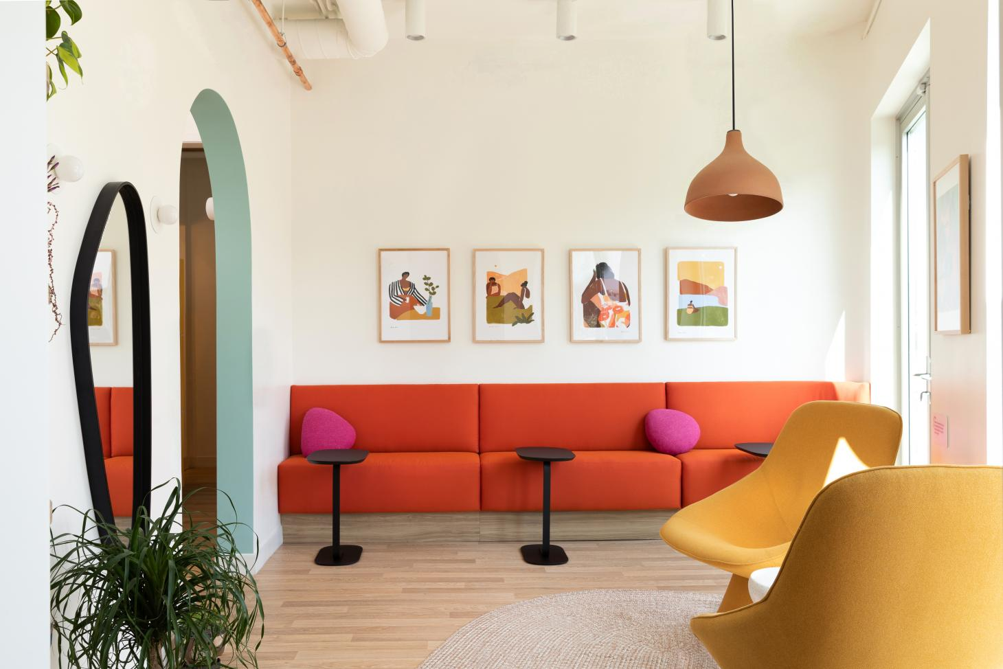waiting room with bright orange sofa at healthcare start-up Tia's new space by Alda Ly