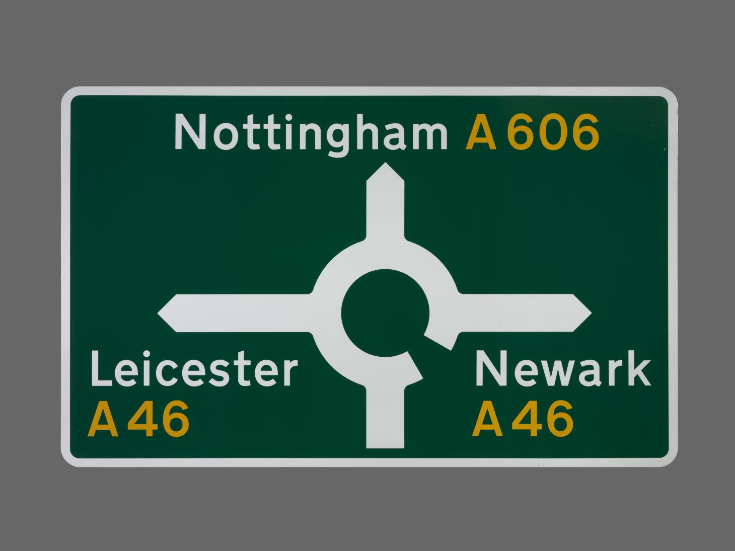 A road sign designed by Margaret Calvert and Jock Kinneir. The green background of the sign features a roundabout symbol with words, Nottingham A606, Leicester A46, Newark A46, written in white and yellow type