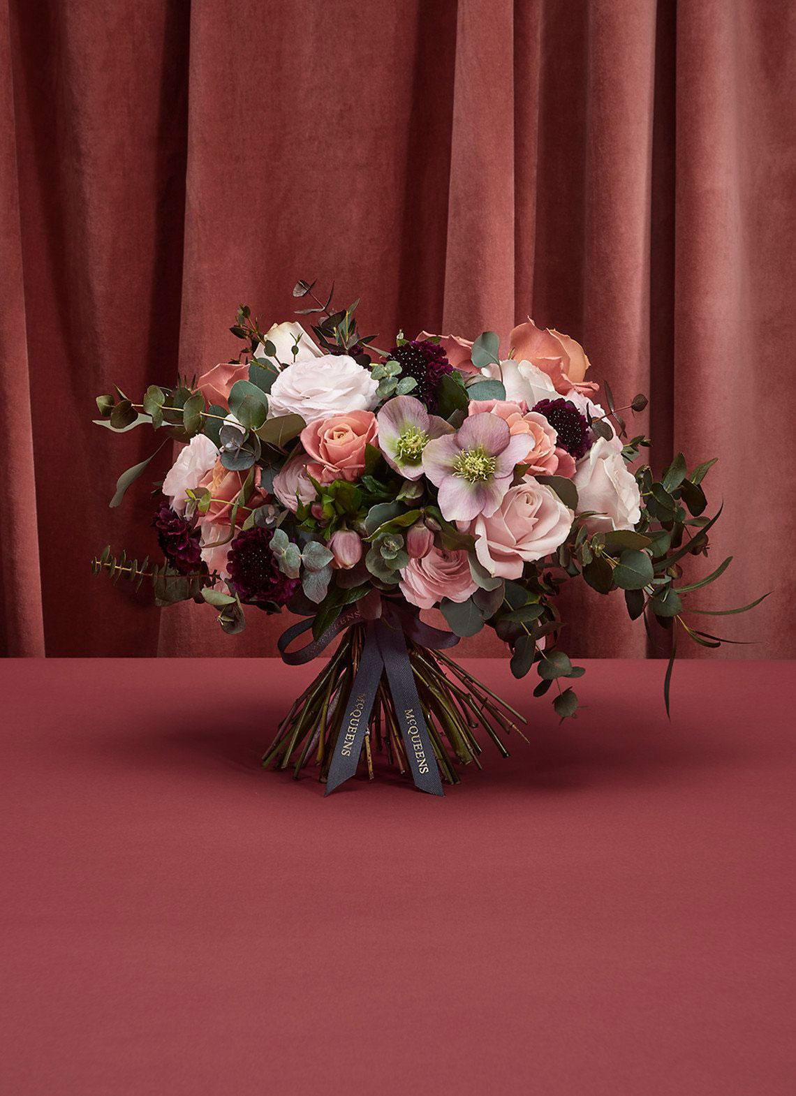 McQueen's flowers of London, Seoul, and New York bouquet of pink and white flowers and green stems against pink background