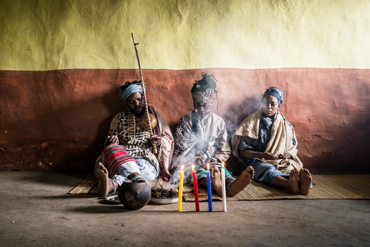 Three men sitting on the floor of a traditional dwelling in Eastern cape behind four lit candles