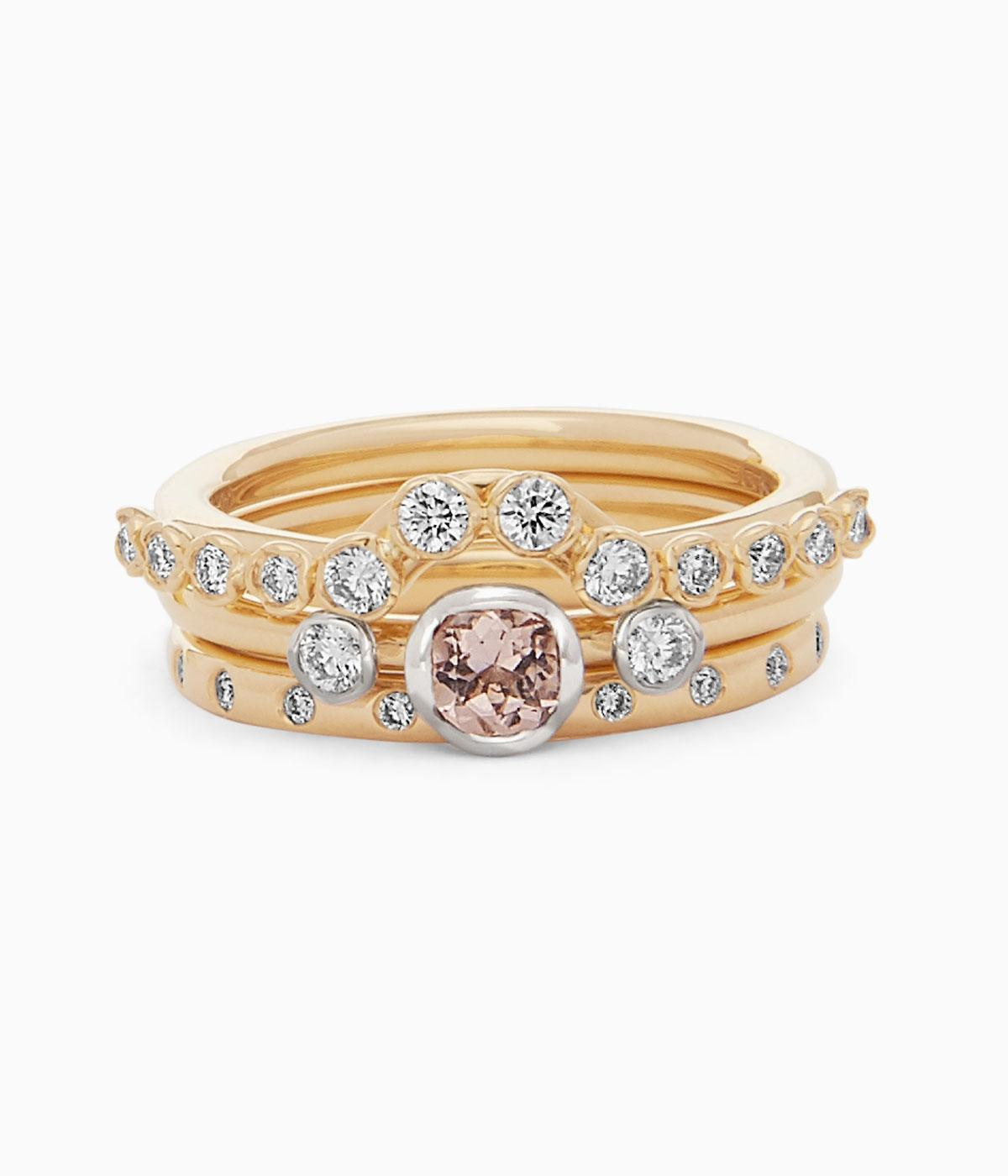 Gold engagement ring with pale red main stone and studded in diamonds on the band