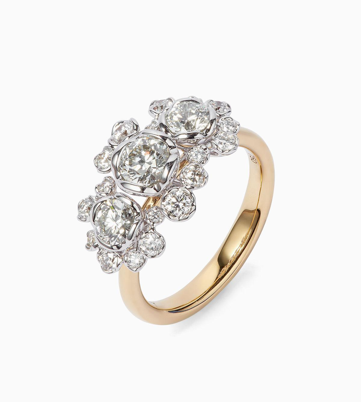 Gold engagement ring with diamonds of different sizes clustered together