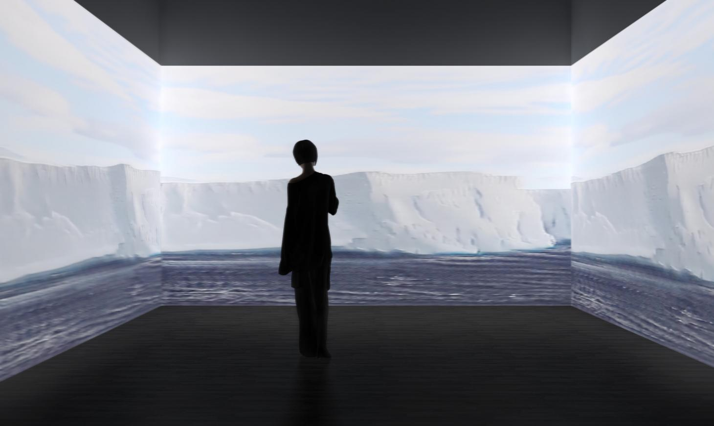 A visitors watches three screens with projection of ice landscape from Antarctica, part of the Antarctic pavilion at London Design Biennale