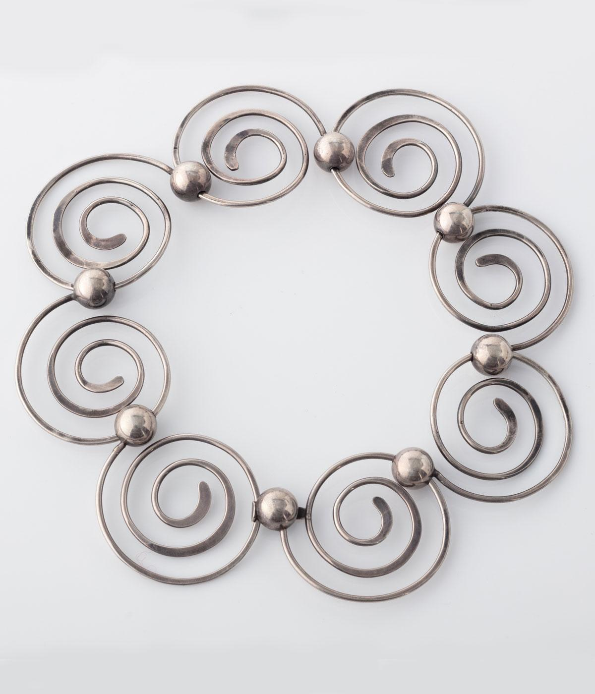 Silver spiral necklace against a grey backround