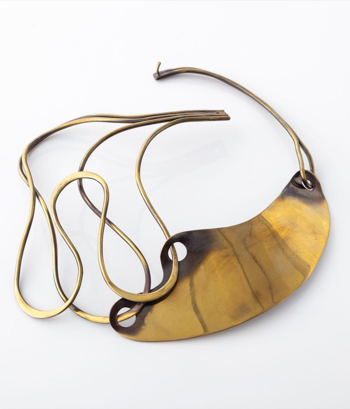 Gold curved necklace against a grey background