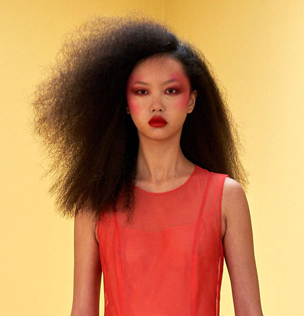Molly Goddard A/W 2021 model with frizzy hair, red lipstick, and bright pink blush