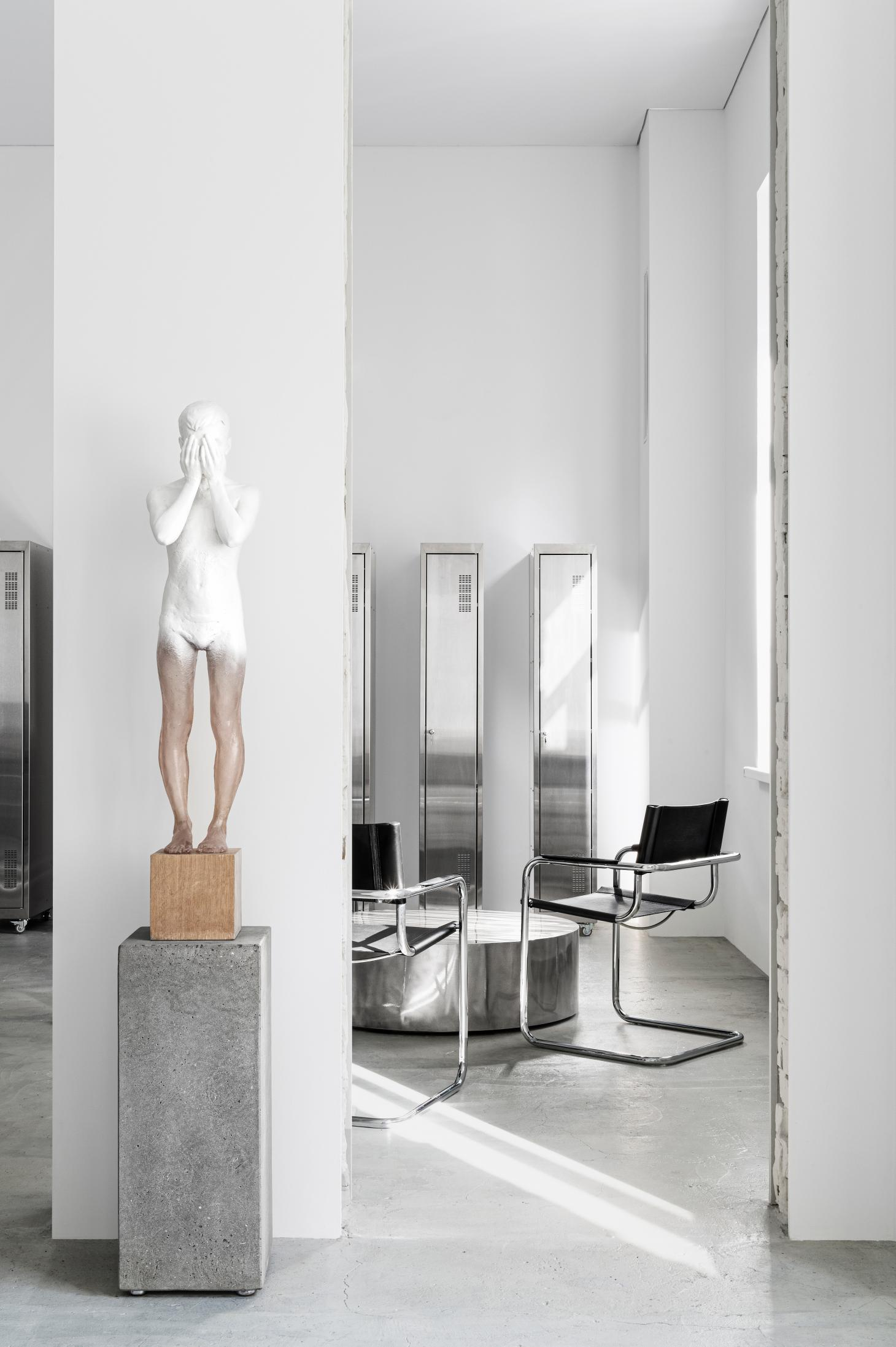 19 tattoo studio in Kiev Ukraine. With black Mark Stam chairs, sculpture of a young boy, and art instillation by propro