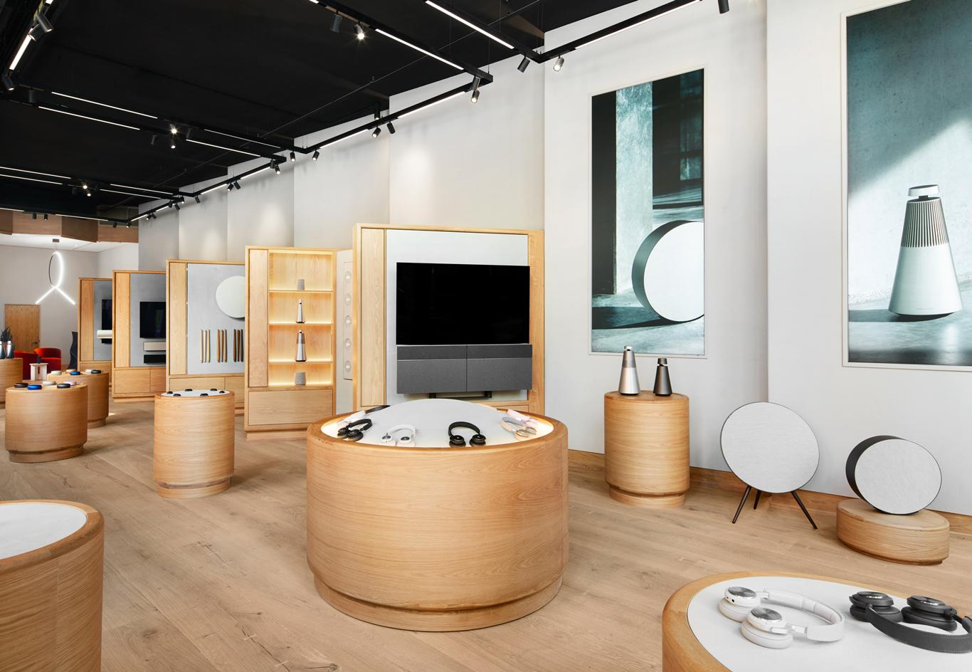 Bang & Olufsen speakers and headphones sit on wooden shelves the flagship shop in NYC
