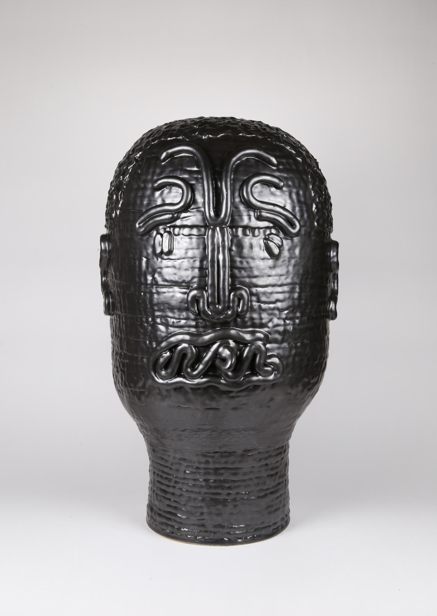 Black ceramic sculpture depicting a human face in stylized form