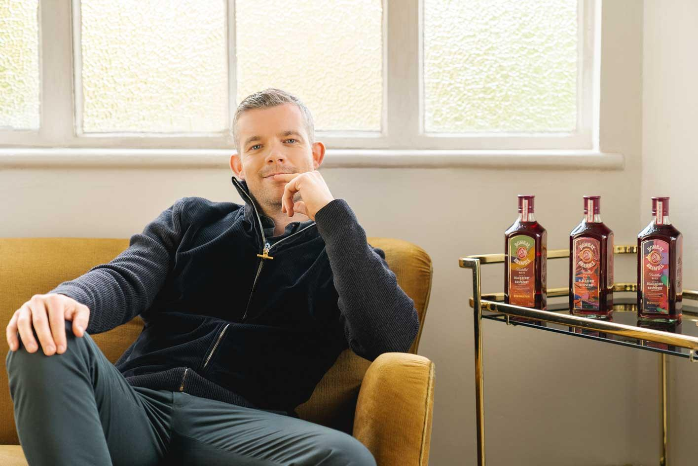 Actor and host of podcast 'Talk Art' Russell Tovey with the limited-edition bottles from his new curatorial project with Bombay Sapphire