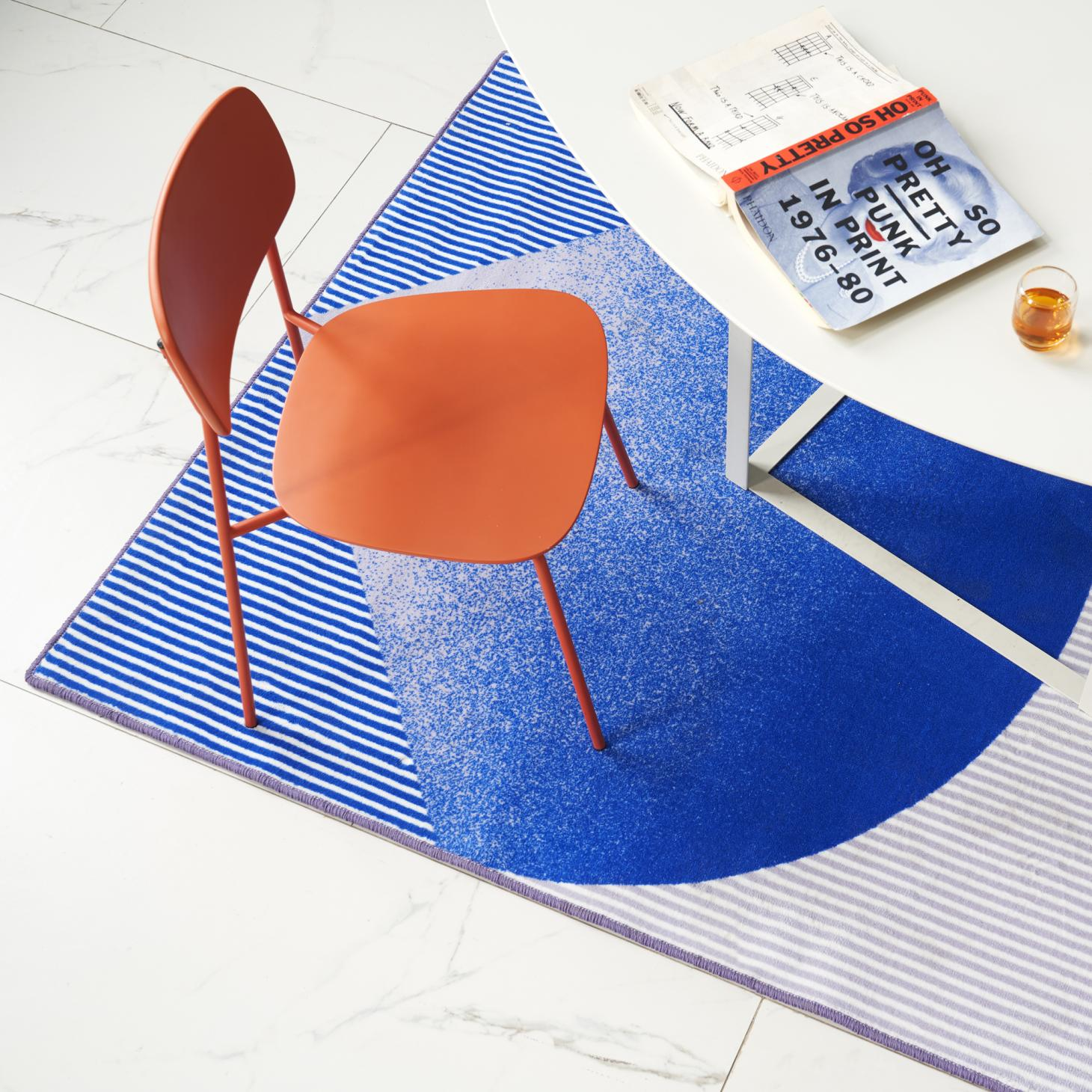 A blue rug by BCXSY for ZaoZuo pictured under a white table and red chair