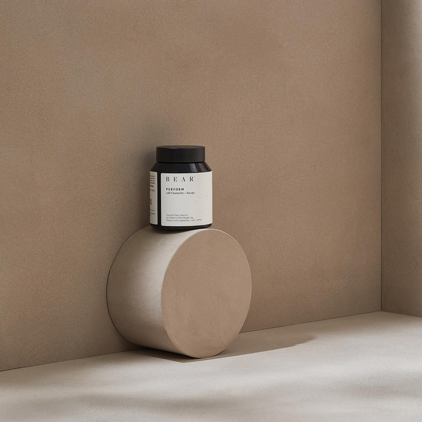 Black supplements bottle displayed against a beige wall