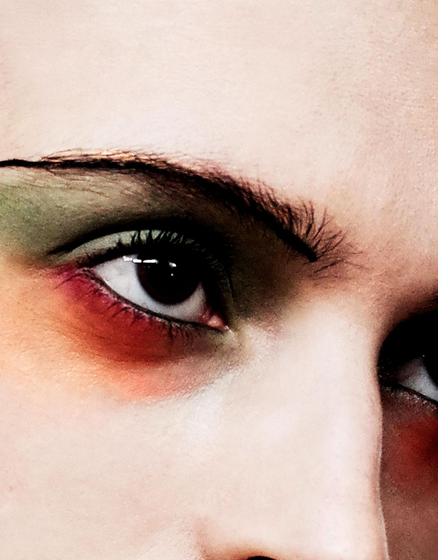 close up shot of girl with green and orange eyeshadow and black line of eyebrow
