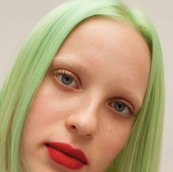 light green hair colour green juice by Bleach London with red lips and bleached eyebrows
